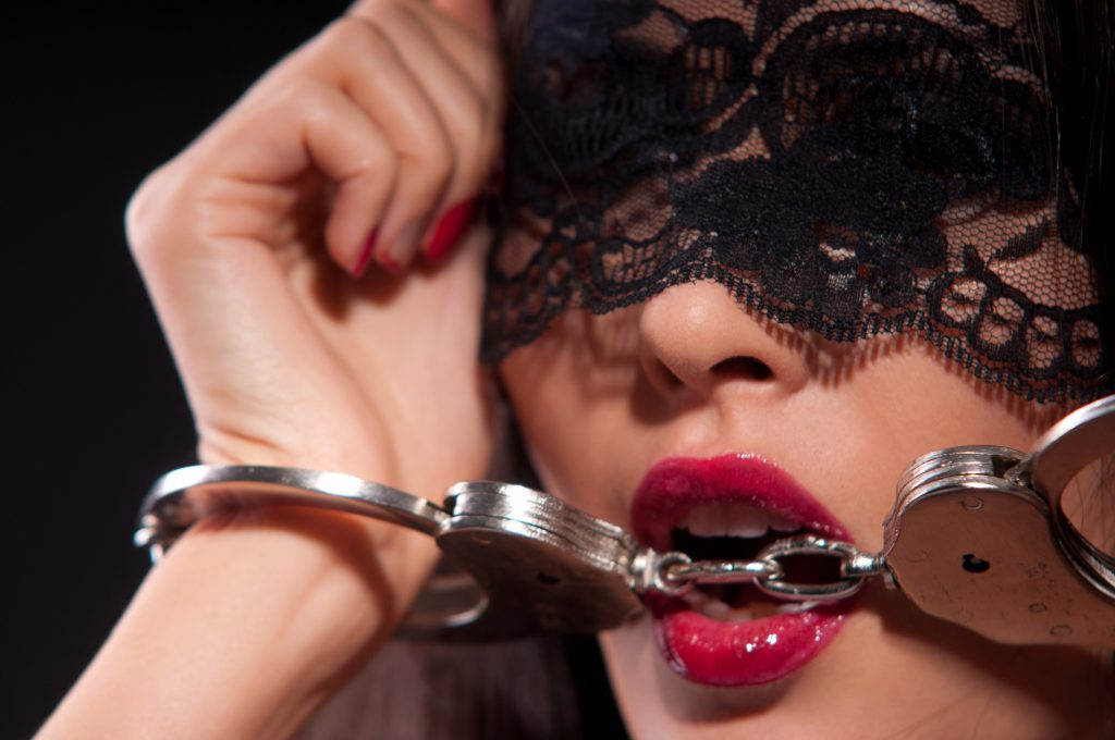 A pretty woman biting handcuffs.